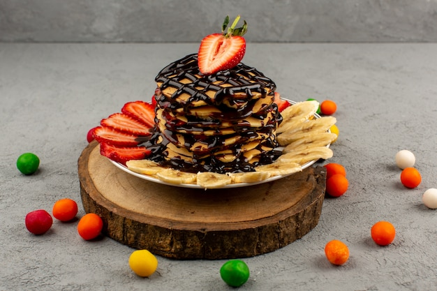 Вид сверху вкусные блины вкусного шоколада вместе с нарезанной красной клубникой и бананами внутри белой тарелки на коричневом столе и сером полу