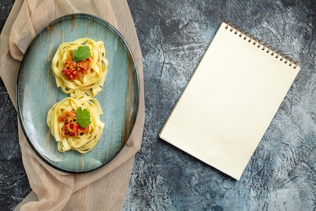 Top view of delicious pasta meal on a blue plate served with tomato and meat for dinner on tan color towel next to closed notebook