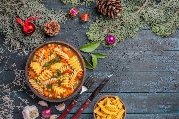 紺色のデスクディッシュ料理カラースープパスタにスパイラルイタリアンパスタからのトップビューおいしいパスタスープ