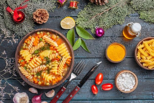 ダークブルーの素朴なデスク料理のスパイラルイタリアンパスタからのトップビューおいしいパスタスープスープパスタカラーディッシュ
