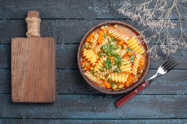 Вид сверху вкусный суп-паста из спиральной итальянской пасты с зеленью на темно-синем столе обеденное блюдо итальянская паста-суп соус