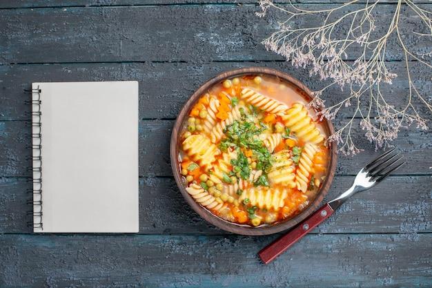 紺色の机の上の緑とスパイラルイタリアンパスタからのトップビューおいしいパスタスープディナーディッシュイタリアンパスタスープソース