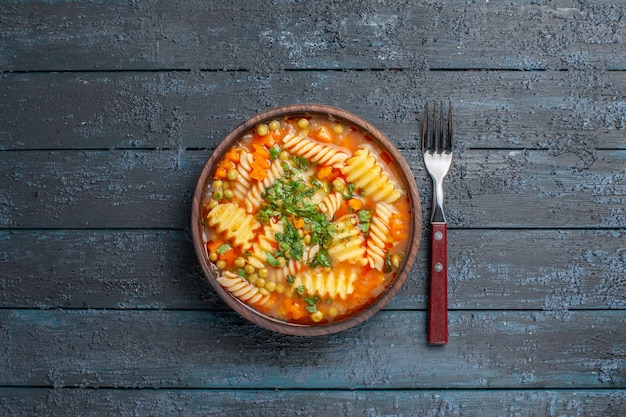 トップビューダークデスクディナーディッシュにグリーンのスパイラルイタリアンパスタからのおいしいパスタスープイタリアンパスタスープソース