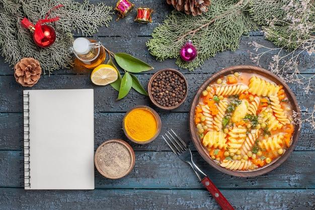 ダークブルーのデスクディナー料理に調味料を加えたスパイラルイタリアンパスタのトップビューおいしいパスタスープパスタカラーディッシュスープ