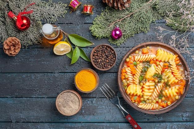 紺色のデスクディナー料理に調味料を加えたスパイラルイタリアンパスタのトップビュー美味しいパスタスープパスタスープカラーディッシュ