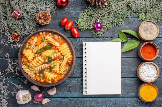 ダークブルーの素朴なデスク料理に調味料を加えたスパイラルイタリアンパスタのトップビュー美味しいパスタスープスープパスタカラーディッシュ