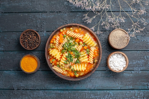 Top view delicious pasta soup from spiral pasta with seasonings on dark-blue desk sauce cuisine dish italian pasta soup