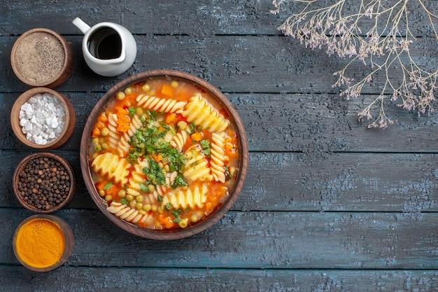 紺色のデスクソース料理に調味料を加えたスパイラルパスタのトップビュー美味しいパスタスープイタリアンパスタスープ