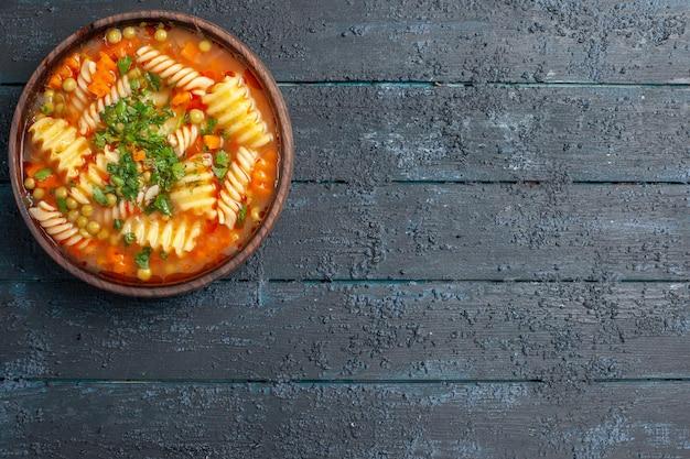 Vista dall'alto deliziosa zuppa di pasta con verdure e verdure all'interno del piatto sul piatto da scrivania scuro cena italiana con zuppa di pasta