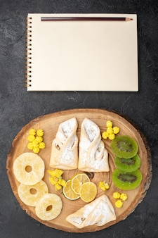Top view delicious pastries with dried fruit slices on grey desk