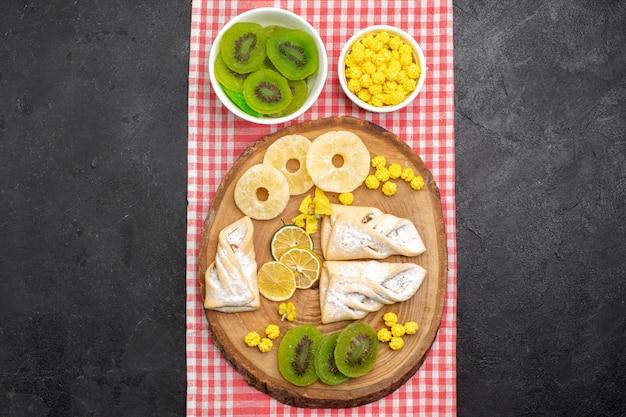 ダークグレーのスペースに乾燥パイナップルリングとキウイを添えたトップビューのおいしいペストリー