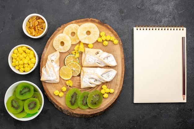 Вид сверху вкусной выпечки с сушеными кольцами ананаса и киви на сером столе