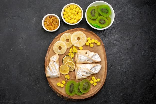 Vista dall'alto deliziosi pasticcini con anelli di ananas essiccati e kiwi sulla scrivania grigio scuro