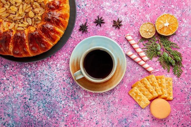 ピンクの机の上にレーズンティーとクラッカーとトップビューのおいしいペストリーケーキ