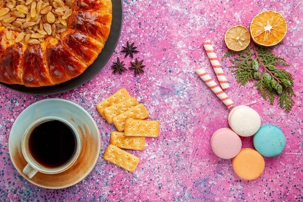 ピンクの机の上にレーズンティーマカロンクラッカーとトップビューのおいしいペストリーケーキ