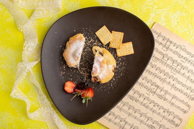 黄色のテーブルのクラッカーとプレート内部のおいしいペストリーのトップビュー、甘いお茶のペストリーを焼く