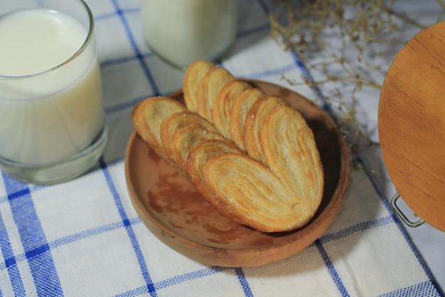 우유 한 잔을 곁들인 나무 접시에 있는 맛있는 페이스트리