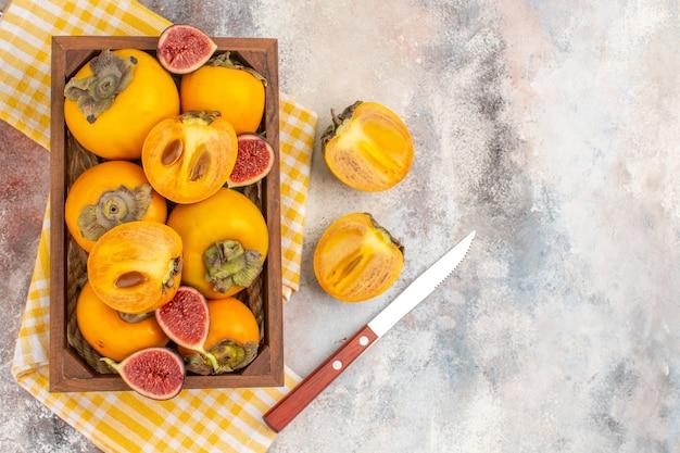 Вид сверху вкусной хурмы и нарезанного инжира в деревянной коробке, желтое кухонное полотенце, нож на обнаженном фоне