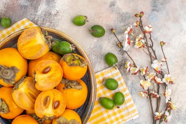 Vista dall'alto deliziosi cachi in una ciotola asciugamano da cucina giallo feykhoas ramo di fiori di albicocca su sfondo nudo