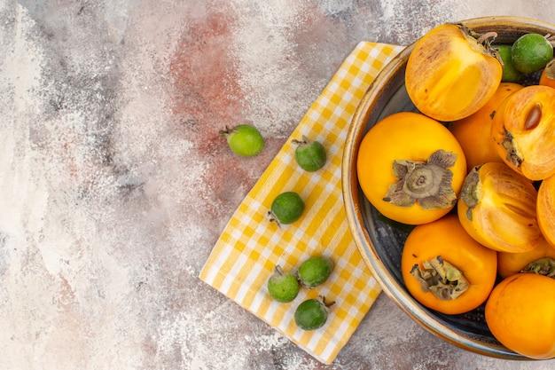 Vista dall'alto deliziosi cachi in una ciotola giallo asciugamano da cucina feykhoas su sfondo nudo