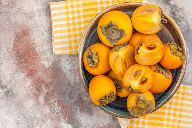 Vista dall'alto deliziosi cachi in una ciotola asciugamano da cucina giallo su sfondo nudo