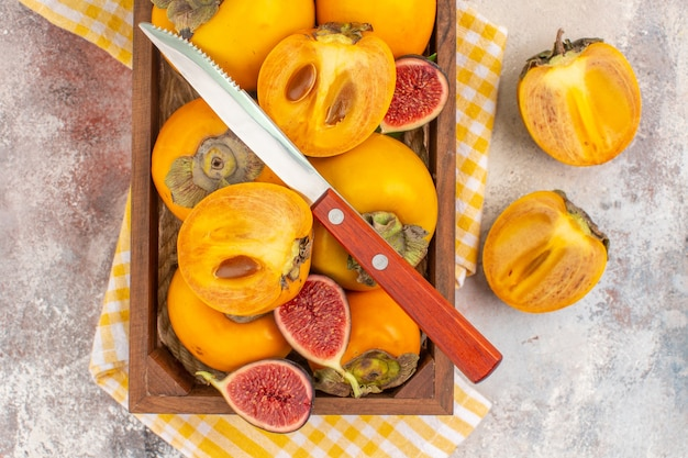Vista dall'alto deliziosi cachi tagliati fichi e un coltello in una scatola di legno su sfondo nudo