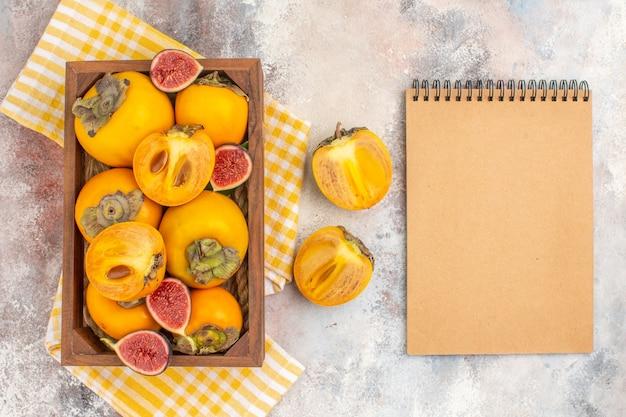 Vista dall'alto deliziosi cachi e fichi tagliati in una scatola di legno asciugamano da cucina giallo un quaderno su sfondo nudo