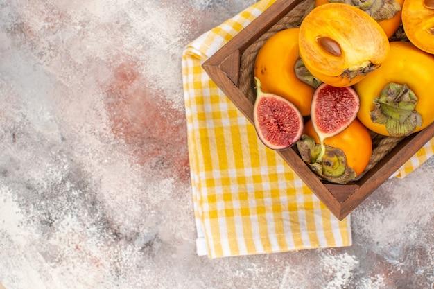 Vista dall'alto deliziosi cachi e fichi tagliati in una scatola di legno gialla un asciugamano da cucina su sfondo nudo