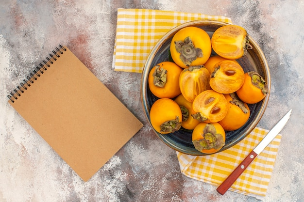 トップビューボウルナイフ黄色のキッチンタオルでおいしい柿ヌード背景のノート