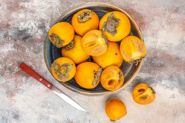裸の背景にボウル柿とナイフでおいしい柿の上面図