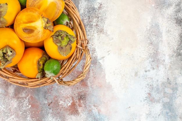 ヌードの背景に籐のバスケットのトップビューおいしい柿