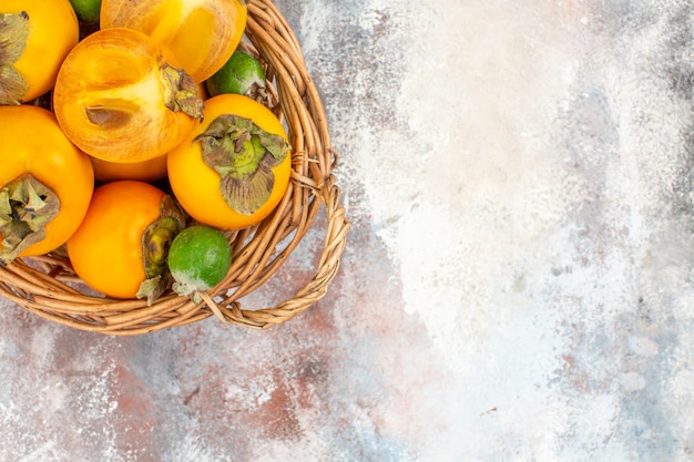 Top view delicious persimmons in wicker basket on nude background