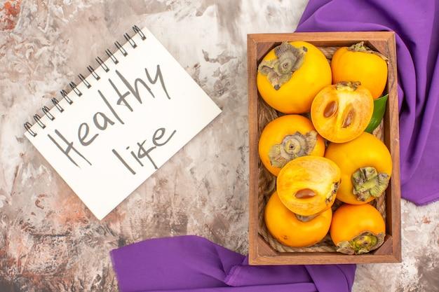 Vista dall'alto deliziosi cachi in una scatola di legno vita sana scritta su taccuino scialle viola su sfondo nudo
