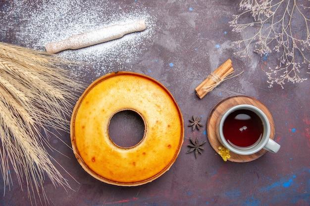 어두운 배경 차 달콤한 파이 케이크 비스킷 반죽 설탕에 차 한잔에 대한 상위 뷰 맛있는 파이 완벽한 달콤한 케이크