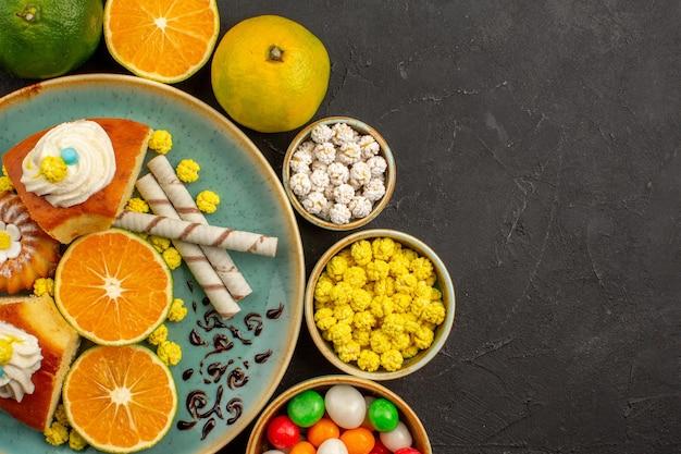 Вид сверху вкусные кусочки пирога с конфетами и свежими мандаринами на темном фоне фруктовый торт сладкий бисквитный пирог