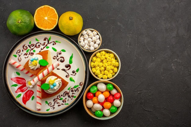 Top view delicious pie slices with candies and fresh tangerines on dark background cake sweet biscuit pie fruit