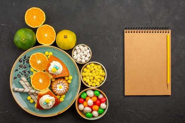 Top view delicious pie slices with candies and fresh tangerines on dark background fruits cake sweet biscuit pie