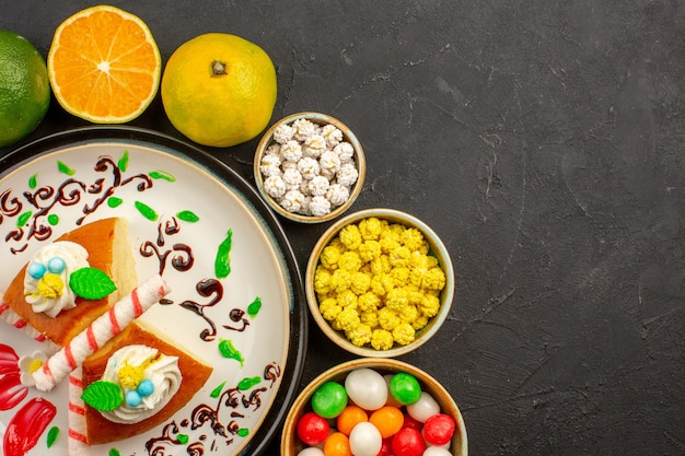 Top view delicious pie slices with candies and fresh tangerines on dark desk cake sweet biscuit pie fruit