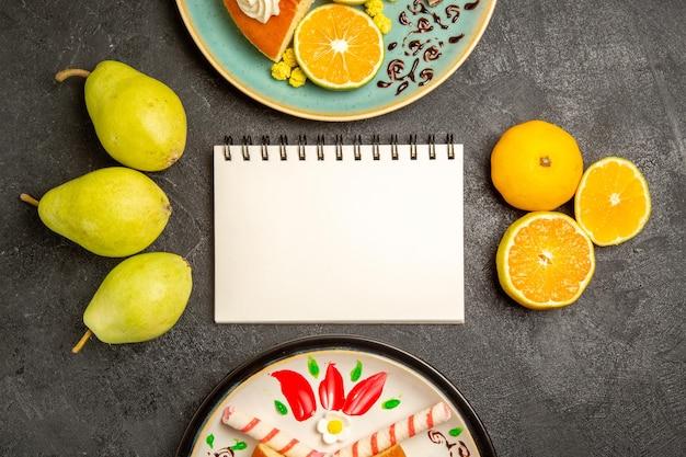 灰色の机の上の新鮮なみかんとおいしいパイスライスの上面図パイフルーツキャンディー生地ティーケーキ