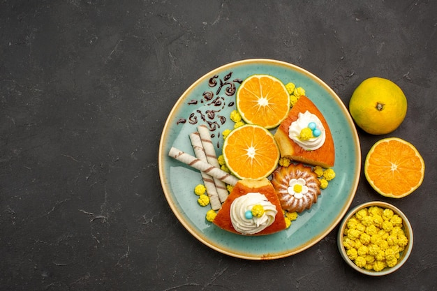 Top view delicious pie slices with pipe cookies and fresh sliced tangerines on dark background fruit cake pie sweet biscuit