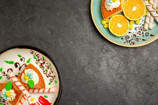 Vista dall'alto deliziose fette di torta con mandarini a fette su sfondo grigio scuro torta di caramelle alla frutta pasta per torta tè