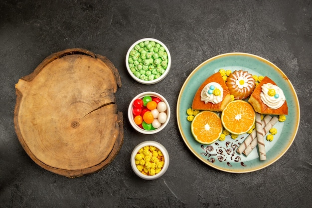 Top view delicious pie slices with tangerines and candies on a dark-grey background fruit candy cake pie dough tea