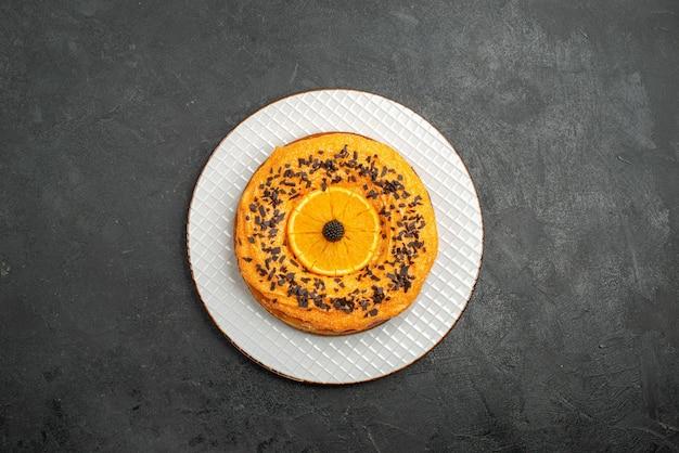 暗い表面のパイデザートケーキティーフルーツビスケットにチョコレートチップとオレンジスライスが付いた上面図のおいしいパイ