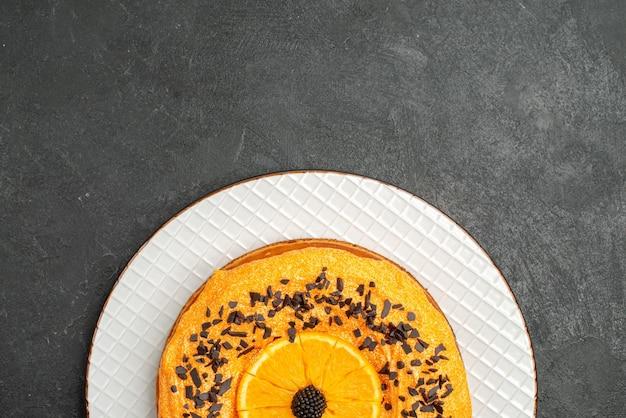 ダークデスクのパイデザートケーキティーフルーツビスケットにチョコレートチップとオレンジスライスを添えたトップビューのおいしいパイ