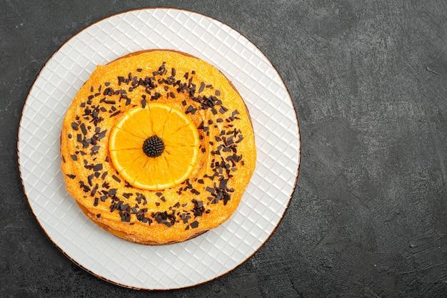 Вид сверху вкусный пирог с шоколадной стружкой и дольками апельсина на темной поверхности пирог десертный торт чай фруктовый бисквит