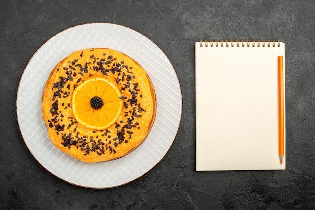 Vista dall'alto deliziosa torta con scaglie di cioccolato e fette d'arancia su superficie scura, dessert, torta di tè, biscotto