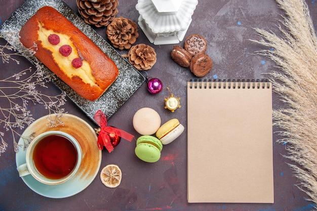 暗い背景にフレンチマカロンとお茶を添えたトップビューのおいしいパイケーキシュガークッキーパイ甘いビスケットティー