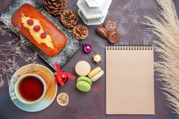 Vista dall'alto deliziosa torta con macarons francesi e tazza di tè su uno sfondo scuro torta zucchero biscotti torta dolce biscotto tè