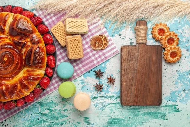 Вид сверху вкусный пирог с вафлями macarons и свежей красной клубникой на синей поверхности
