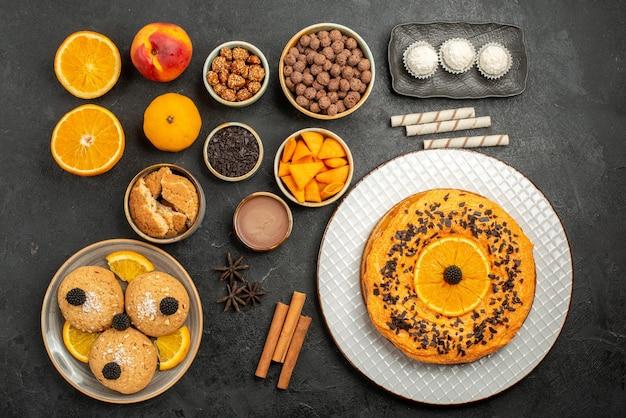 暗い表面のティービスケットフルーツデザートパイケーキにオレンジスライスとクッキーが付いた上面図のおいしいパイ